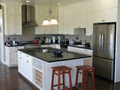 cuisine blanche avec plan de travail noir aux tabourets de bar de style classique en bois