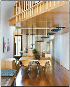 The addition's most eye-catching feature is the steel staircase with recycled blackbutt wood treads. The bottom steps double as benches to supplement the six Arne Jacobsen Series 7 dining chairs for Fritz Hansen and a Nomos table base by Sir Norman Foster for Tecno.  Courtesy of Vang@taverne-agency.com.