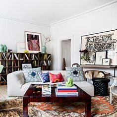 The duo split up the apartment's single open living space into a lounge area, an entryway-slash-library, and a dining nook. Ouellette kept the Ligne Roset sofa and French bergére chairs in neutral hues. Silk Bermingham & Co. pillows and a red-lacquer coffee table from Atelier Midavaine in Paris add pops of rich color.