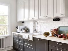 Black and white kitchen with white top cabinets and black bottom cabinets paired with white countertops and subway tile backsplash. Fabulous kitchen features white apron sink accented with gooseneck faucet as well as hidden dishwasher disguised behind cabinet door.