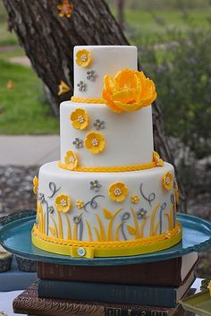 Round tiered cake with gray and yellow flower details (link does not lead to a tutorial).