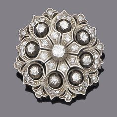 A late 19th century diamond brooch, circa 1880 The circular pierced plaque set with old brilliant and rose-cut diamonds, mounted in silver and gold, old brilliant-cut diamonds approx. 2.00ct. total, later brooch fitting, diameter 4.9cm.