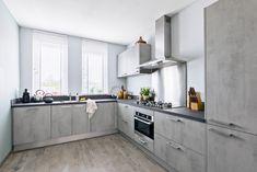Thuis bij Jeffrey. 'We zochten een mooie, maar vooral ook functionele keuken' Het werd een ruime L keuken in de kleur betongrijs.