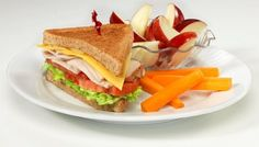 Friendly's Half Turkey Sandwich: Sliced turkey and American cheese on toasted wheat bread with lettuce, tomato and honey mustard paired with apple slices and carrot sticks. Analysis includes water for choice of beverage.