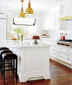 Tour a traditional kitchen with a glam touch// Black and white kitchen design with brass island pendants