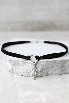 """The Found Treasures Black and Silver Choker Necklace is a discovery worth holding on to! Velvety vegan suede choker has a silver O-ring and feather charm at center. Necklace measures 13"""" with a 2"""" extender chain."""