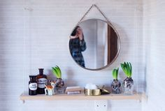 Small wooden shelf hung with rope and hooks.