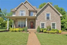 love the color of the brick, the front porch, the clean, simple landscape and door color...