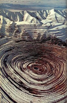 "April 1975  ""The company's [Kennecott Copper] mineral bull's-eye in the Oquirrh Mountains stretches two and a half miles wide and more than half a mile deep - the nation's largest open-pit copper mine, and its most productive.""  From article ""Utah's Shining Oasis"" by Charles McCarry, photo by James L. Amos"