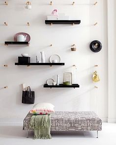 I have always liked Shaker peg rails, such as these classic ones that we've featured in the past . I would love to have one where I could hang chairs and other items when not in use. So when I saw this peg wall, I was fascinated.