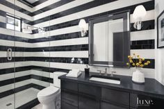 Daltile subway tiles clad a wall in the basement guest bath in a striped black-and-white pattern, continuing the linear play that runs throughout the house.