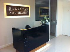 Projeto Ana Donadio - Recepção de um escritório de advocacia. Balcão com iluminação embaixo e logotipo retroiluminado embutido na parede de drywall. Móvel em mdf e laca preta brilhante.