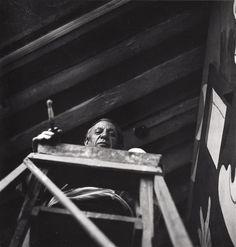 Picasso sur un escabeau, un pinceau à la main devant Guernica, dans l'atelier des Grands Augustins, Paris