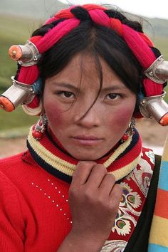 Young Tibetan woman in traditional headdress. The expression in her eyes, looking straight through the camera at you. (V)