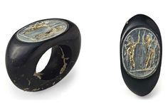 Roman obsidian and gilt glass finger ring, 1st-2nd century A.D. The obsidian hoop slightly convex on the interior, with broad shoulders, the oval bezel set with a pale transparent thin green glass gem engraved with the Dioscuri standing on a groundline, Castor and Pollux both depicted nude, each armed with a crested helmet, holding a spear in one upraised hand, a sheathed sword and a shield in the other, the engraved areas overlaid with gold foil, 3.8 cm wide. Private collection
