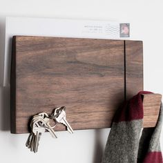 Organize your entryway in style with this multi-purpose wood wall rack. A great look in maple or walnut and a must-have for on-the-go households! <br> <ul><li> Modern design has a built-in mail slot in back for grab and go convenience </li> <li> Made from solid maple or walnut </li> <li> Multi-function front includes a scarf or coat hanger, magnetic key holder and serves as a tack board for important reminders </li> <li>...