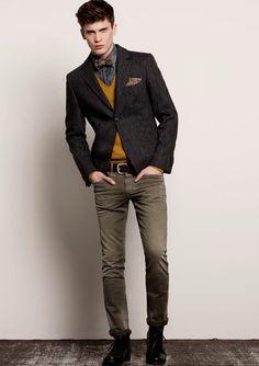 Closed - Dark tweed jacket, mustard v-neck sweater, grey denim shirt, brown bow tie, brown handkerchief, dark brown leather belt, tan jeans, dark brown lace-up boots