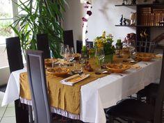 Table décorée avec une écharpe dans les tons des assiettes sur une nappe blanche