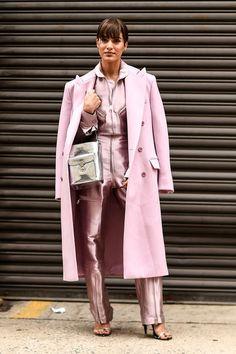 Glanzleistung von Camila Coelho: Die Influencerin trägt zum futuristischen Metallic-Jumpsuit in Rosa von Ralph Lauren einen farblich passenden Mantel und eine silberne Tasche. Vielleicht hat sie in der auch ihre warmen Schuhe versteckt ...
