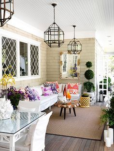 So cozy and bright! Love the light fixtures and wood porch with white ceiling. I would replace the sofa (and lose those pillows) with something more colorful or wood though, I don't like white cloth furniture very much.