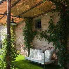 Bout de jardin avec son lit en fer forgé à l'ombre.