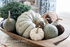 Love the simplicity of this centerpiece of kale, pinecones, and squash in a wooden trough.