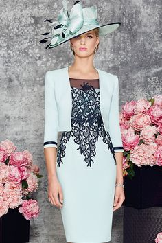 Knee length fitted dress with sweetheart neckline. The neck is overlaid with a fine mesh which creates a high neck and sleeves. The body of the dress is covered in a heavy contrasting lace giving a very elegant silhouette. The jacket is short and fits to the waist. Product Code: 008894 Colour: Navy/Aqua