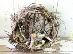 One of a kind Woodland Fairy House whimsical hanging basket fairy houses nature art by Laurie Rohner.   Woodland Fairy House is one of a kind whimsical sculpted hanging basket  fairy house. I altered this woven twig basket turned it on its side and  placed branches in the back. Along the bottom is an enchanted magical  fairy vignette with chairs cut from branches and stools by tables with  moss and pine cones lichen and sea glass tucked in the nooks. My   woodland  fairy vignette is a fun…