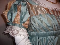 As the slim  'Directoire' styles became more elaborate, moving towards the early Romanticism of the 1820s, detailing became more complex. Detail of a ball gown, featuring seafoam-blue silk, cloth of gold gauze and lace; styled after an extant gown.