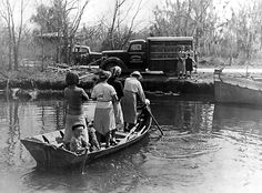 Readers cross the Bayou de Large by boat to get to the Louisiana Library Commission's bookmobile, 1930s.