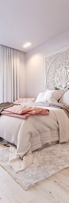 This tranquil white bedroom design is perfect for a small bedroom space. The medallion on the wall adds a touch of bohemian glamour to the room as well as the soft shades of chocolate, blush, and grey.