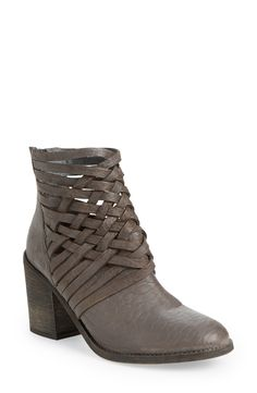 Crisscrossed straps heighten the vintage aesthetic of this caged bootie crafted from weathered leather and lifted by a chunky stacked heel.