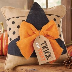 "witch hat and witch legs.  Burlap pillow wrap features dimensional witch hat with contrasting bow and printed ""trick or treat"" burlap tag on polka dot background. Fastens at back with Velcro."