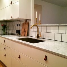 Vårt nya kök! Vita luckor, bänkskivor i carraramarmor och blandare i rå mässing samt beslag i läder och mässing.