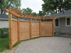 Lattice screening with pergola top provides privacy from neighbor at this home in Richfield. Vines now soften this structure, along with hanging baskets. Design by Steve Wilde.