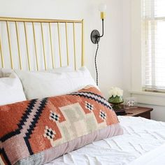 kilim pillow and brass bed