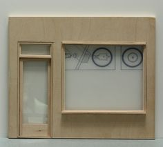 Simple dollhouse shop with a plain front window fitted and held in place with trim.