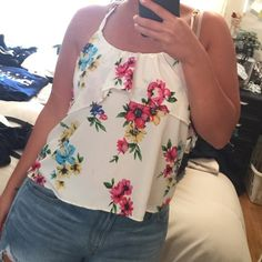 Floral Top NWT White with floral design. Cross cross back. Ruffle tier. Very cute ! NWT Tops Blouses