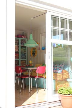 Fabricaholic's colourful dining area, with retro textiles and industrial light shade - probably doubles as a sewing space.
