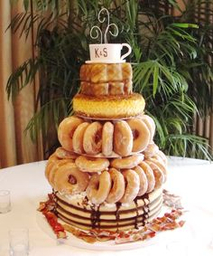 "breakfast cake - the groom was a very pick eater, he eats breakfast food for dinner, so I made a breakfast wedding cake for the reception dinner. 14"" carved to make ""pancakes"", real krispy kreme donuts for 2 tiers. 8"" single layer for ""hashbrowns"" 5"" square as ""texas toast"" gumpaste coffee cup. gumpaste bacon around the base of the cake. Lots of fun, loved this cake!"