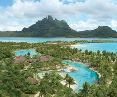 """St. Regis Resort Bora Bora, set on a motu, or islet, on island's coral reef, was created as """"a kind of village,"""" says the architect, Pierre Lacombe. Villas, secluded by palm groves, wind along the beaches. On its own island in the lagoon is the Royal Estate, a 13,000-square-foot villa. (April 2008)"""