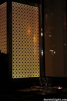 An oriental style room divider wall made from translucent glass and patterned metal sheet, lit from behind with LED strips below. - in London, United Kingdom