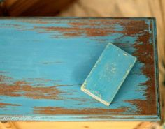 Using a sanding sponge to get the perfect distressed paint finish.