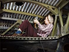 """October 1942. """"Douglas Aircraft plant at Long Beach, California. An A-20 bomber being riveted by a woman worker."""""""