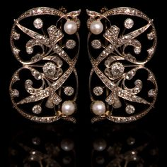 Pair Edwardian diamond and cultured pearl brooches, each set with two cultured pearls with stylised foliate scrolls set with old cut and rose cut diamonds, each brooch measures approx 50mm x 30mm
