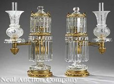 Fine pair of English gilt lacquered brass, gilt, bronze and cut crystal single-light Argand lamps, faceted and knopped oil font, over lobed and pierced prism ring, two-tone gilded standard, on ovoid glass base, with acanthus foot rim, the scrolled arm supporting frosted and wheel-cut shades, England, circa 1845-1855