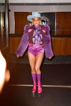 In a suede and fur jacket, paisley blouse, magenta hot pants, multicolored platform boots (courtesy of Marc Jacobs), aviator sunglasses and a blue wide-brim hat while arriving on set at Saturday Night Live.