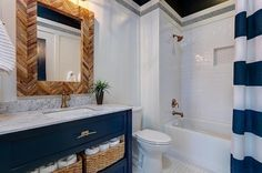 White and blue bathroom boasts a blue vanity adorned with gold pulls topped with gray quartzite fitted with a rectangular white porcelain sink and a gold faucet placed below a wood herringbone mirror alongside a white hex tiled floor. Amazing bathroom features a drop-in tub filled with white subway tiles accented with navy hex border tiles finished with a white and blue awning stripe shower curtain.