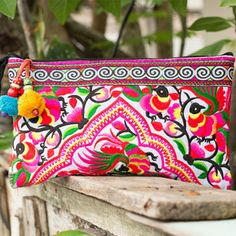 Bring a pop of fun and excitement to what will be going on all around you with colorful handbags to hold all your bridal party's gear. This handmade bag uses fabric made by the HMONG hill tribes of the northern region of Thailand. The unique design makes for a stylish bag like no other.