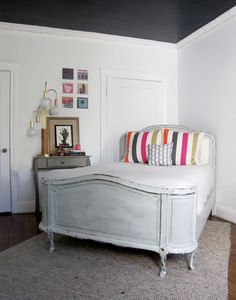 bedroom with black ceiling, striped pillows, vintage french bed
